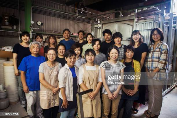 Group portrait of the staff of a Japanese porcelain workshop standing in front of kiln, smiling at camera.