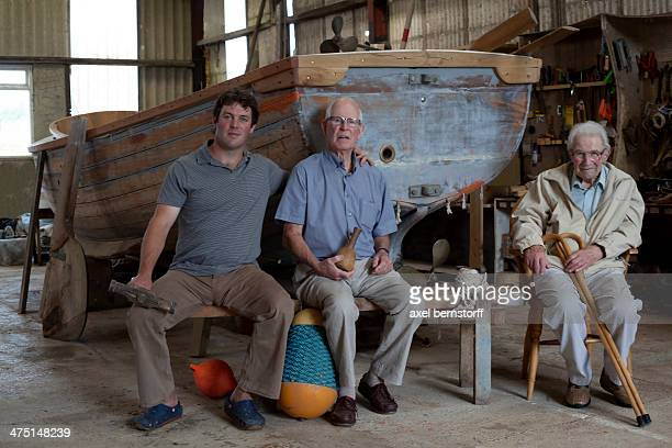 Group portrait of three generations of male boat builders