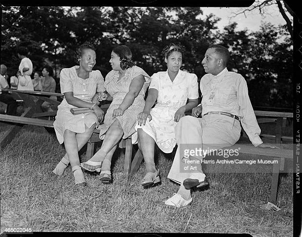 Group portrait of three women including two wearing striped dresses on left and a man wearing ribbon inscribed 'GuestPicnicNorth Park' gathered at...
