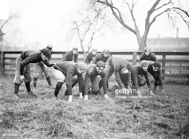 Group portrait of Waller High School football team offensive crouching looking forward preparing to snap the ball on an athletic field in Chicago...