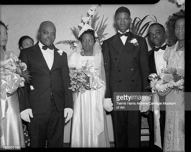 Group portrait of wedding party including bride Johnnie Bell Lewis Leonard wearing short sleeved gown with square neckline and groom Robert Leonard...