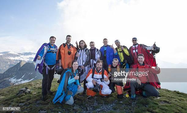 Group portrait of wingsuit fliers relaxing, summit