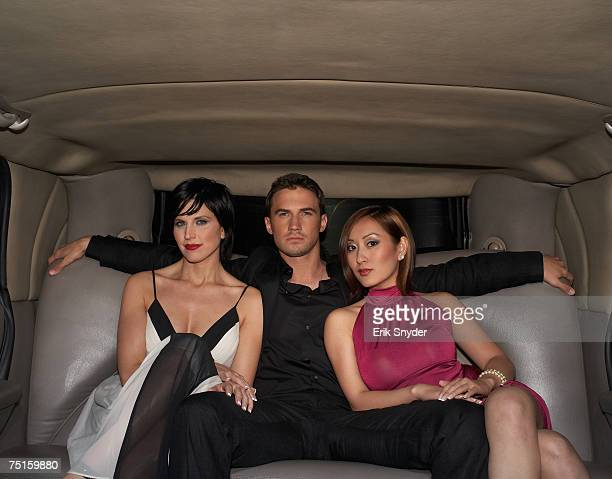 Group portrait of young man and two women sitting in limousine