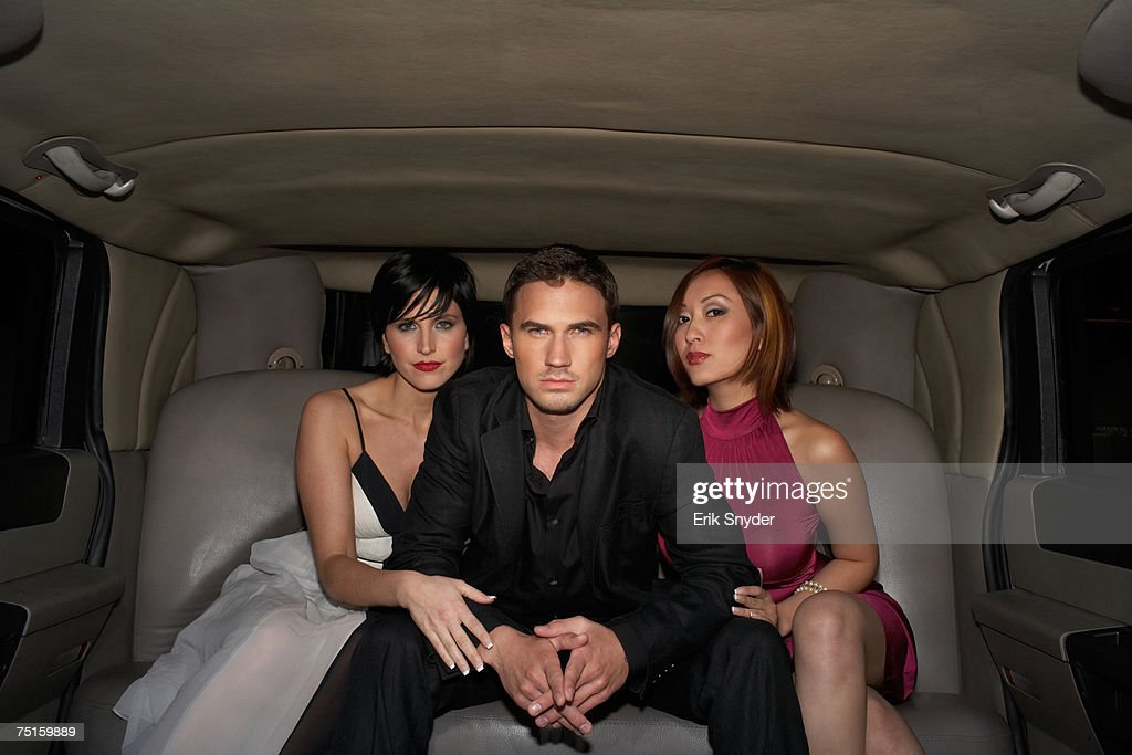 Group portrait of young man and two women sitting in limousine : Stock Photo