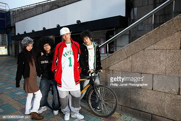 group portrait of young people in street, including teenage boy (16-17) with bicycle - chav stock photos and pictures