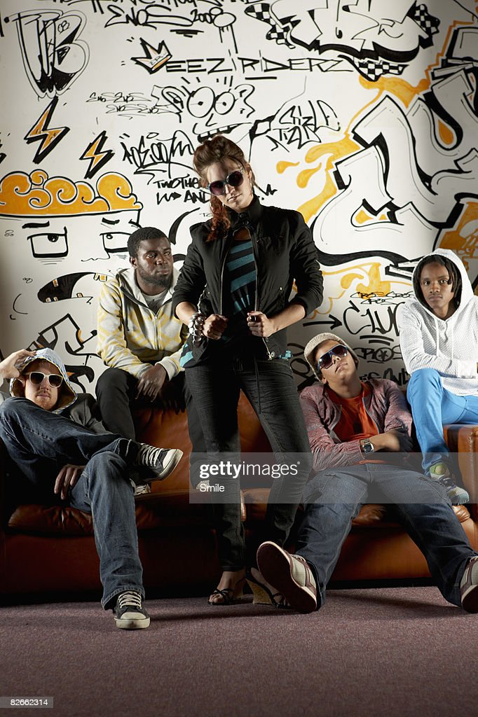 Group posing on couch in front of graffiti wall : Foto de stock
