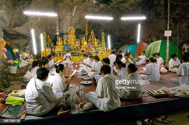 A group praying in the center part of the cave system after taking a meal inside the Wat Tham Bo Ya cave During Khao Phansa anyone in Thailand can go...