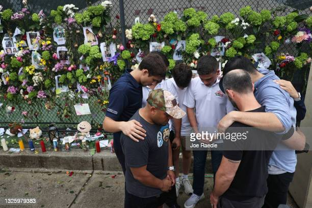 Group prays near where pictures of some of the missing from the partially collapsed 12-story Champlain Towers South condo building hang on a fence on...