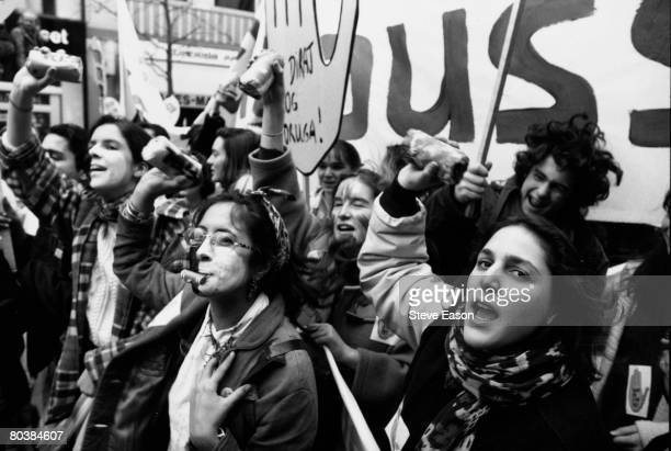 A group protestors with painted faces at an antifascist demonstration in Paris France February 1993