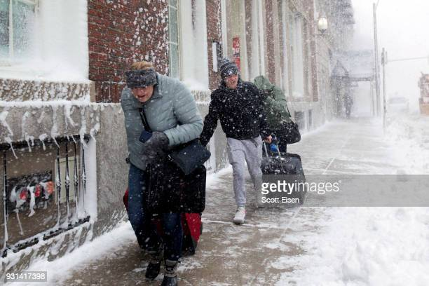 A group pulling luggage walks down Stuart St against high winds and blowing snow as Winter Storm Skylar bears down on March 13 2018 in Boston...
