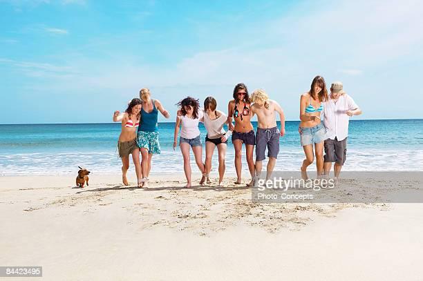 Group racing on beach with dog