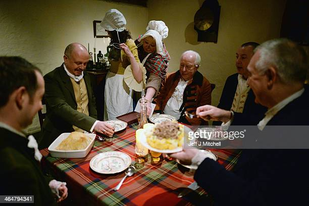 A group reenact the first ever Burns Supper held in 1801 on the fifth anniversary of his death inside the cottage where he was born in 1759 on...