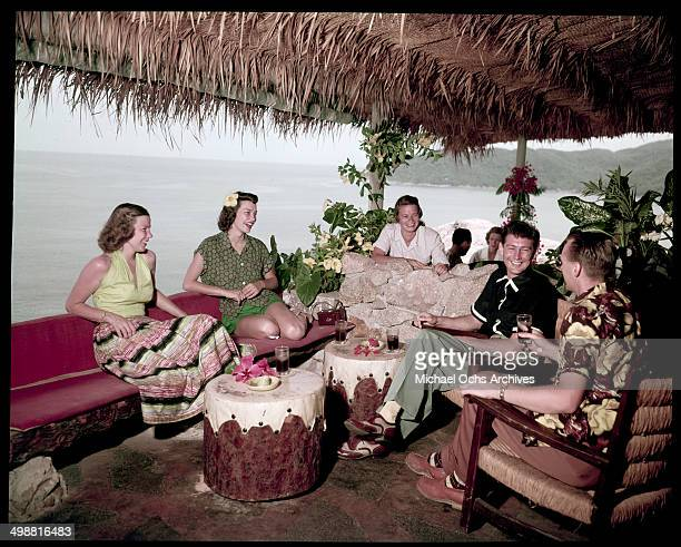 A group relax and talk in a cabana in Acapulco Mexico in July 1953