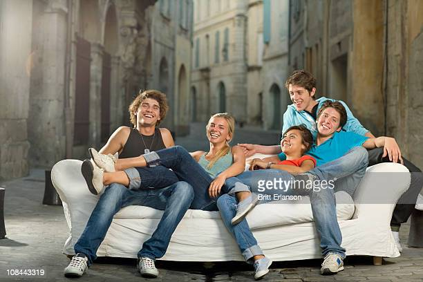 Group relax on couch laughing in street