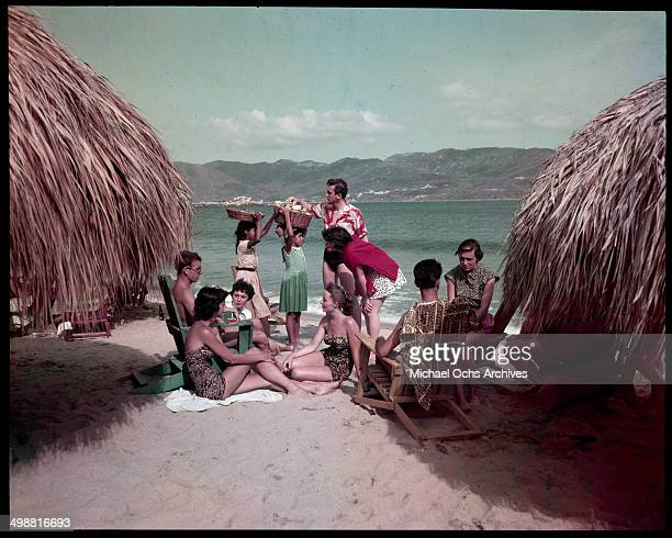 A group rest on the beach as local girls sell items in Acapulco Mexico in July 1953