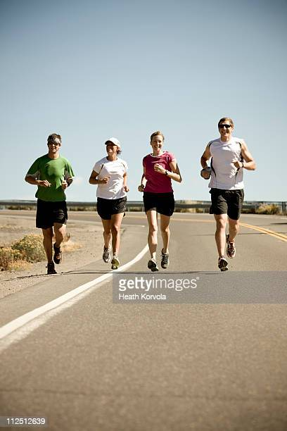 Group running on empty roadway.