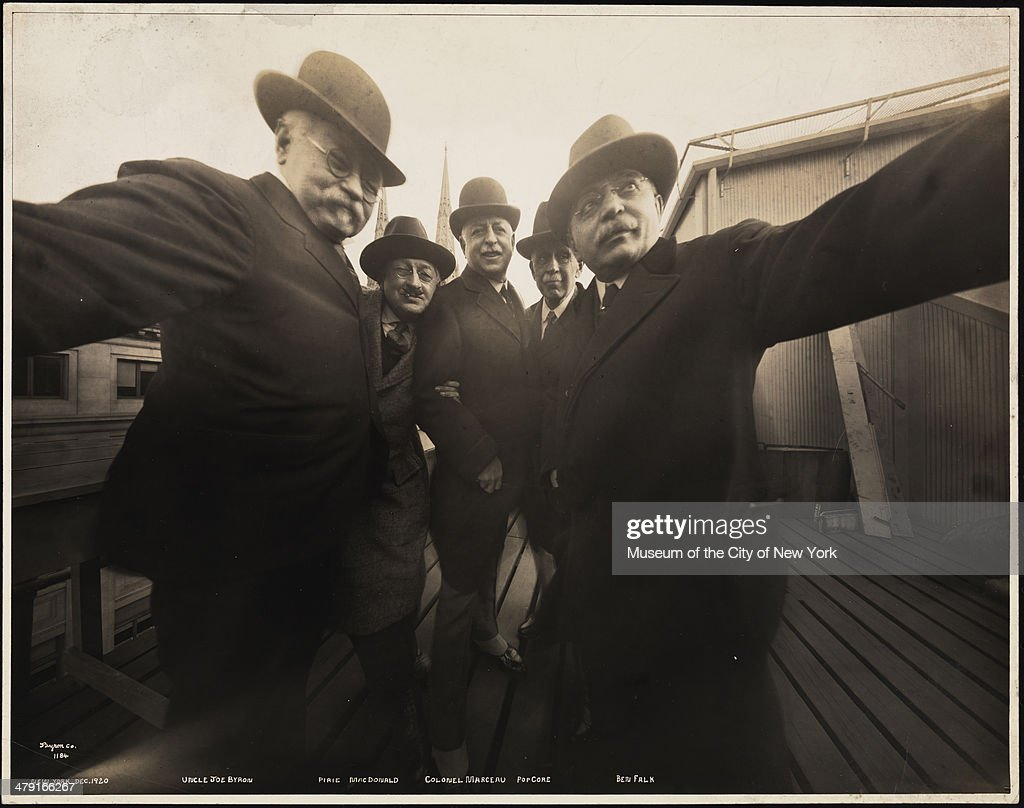 Group self-portrait of five photographers on the roof of Colonel Marceau's photography studio, New York, December 1920. Pictured are, from left, Joseph ('Uncle Joe') Byron (fore, left hand on camera), Pirie MacDonald (second left, in hat), Colonel Marceau and Pop Core (both hidden, and Joseph ('Uncle Joe') Byron (fore, left hand on camera), Pirie MacDonald (second left, in hat), Colonel Marceau and Pop Core (both hidden, and Ben Falk. Byron and Falk each hold a side of the camera.