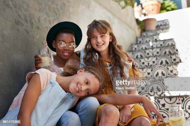 Group shot of 3 girlfriends sitting on staircase