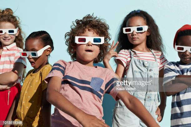 Group shot of cool kids wearing 3-D glasses while playing and posing