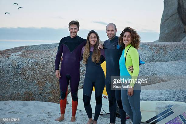 Group shot of surfers in wetsuits on the beach