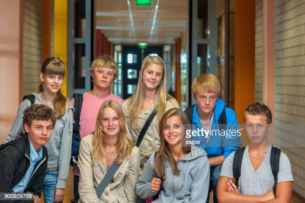 Group shot: three quarter length shot of eight teenage boys and girls with shoulder bags in high school hallway looking at the camera, focus on the girls in the front