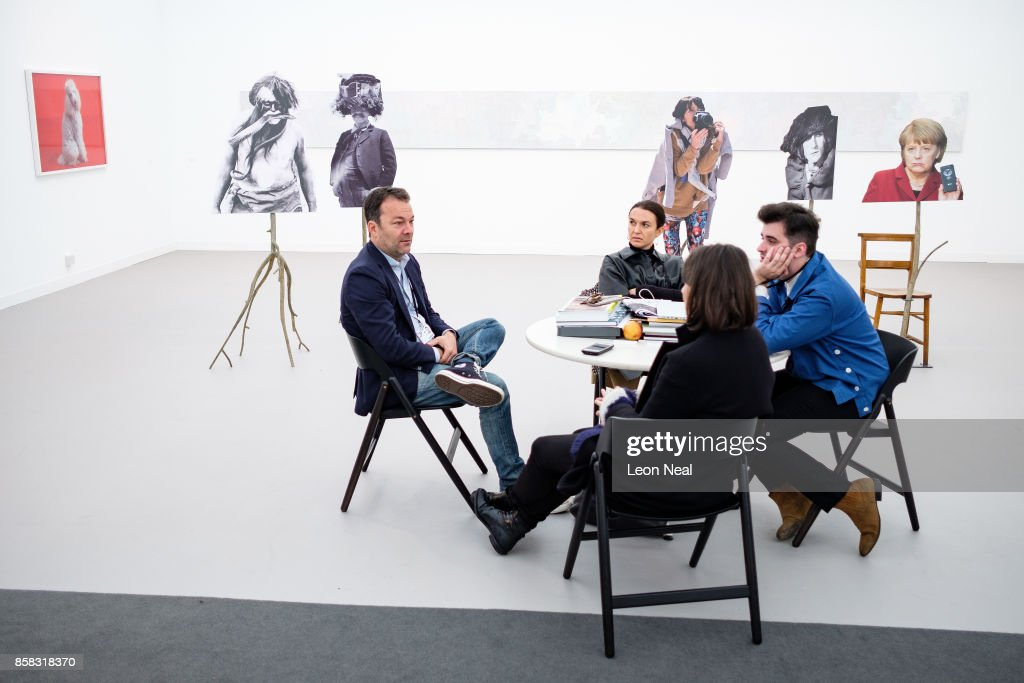 A group sits and talks in front of a range of stand-alone artworks by Goshka Macuga at the Frieze Art Fair on October 6, 2017 in London, England. The annual event sees galleries showcase work by thousands of artists from around the world. The Frieze Art Fair runs from 5-8 October, 2017.