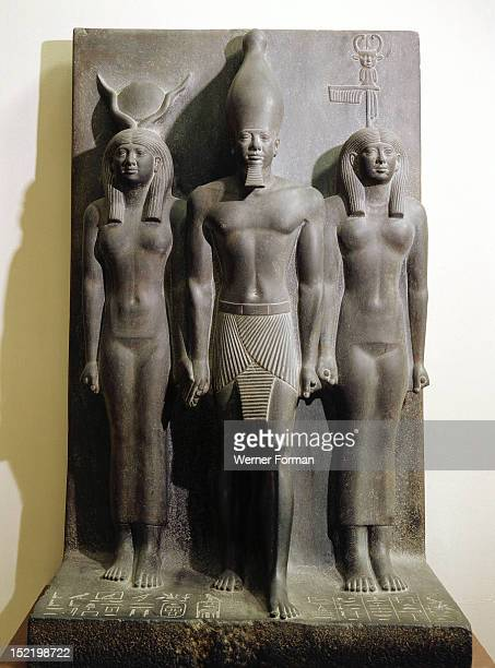 A group statue of King Mycerinus between the goddess Hathor and the personification of the nome of Hu or Diospolis Parva The statue was found in the...