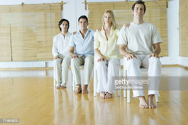 Group therapy, adults sitting in chairs with hands on each other's shoulders