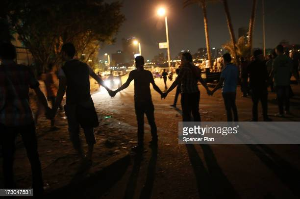 A group tries to keep people away from the 6 of October Bridge following clashes between antiMohammed Morsi crowds and members of the Muslim...
