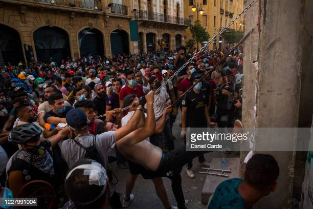 Group uses a chain to bring down a concrete barrier outside of parliament during an anti-government protest on August 10, 2020 in Beirut, Lebanon....