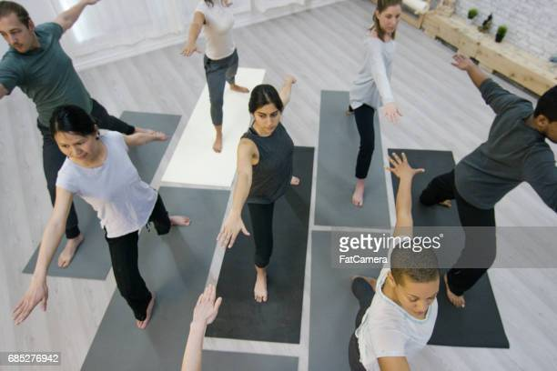group warrior pose - yogi stock photos and pictures