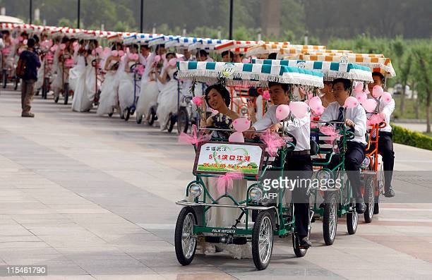 A group wedding couples rides cycle carts as part of a mass wedding ceremony at a park in Wuhan in central China's Hubei province on May 1 2011 The...