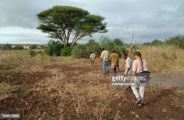 Group woman hiking armed Hadza hunter gatherer Masai guides Northern Tanzania