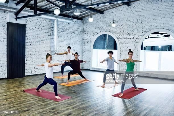 group yoga in loft studio - yoga studio stock pictures, royalty-free photos & images