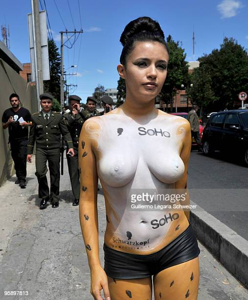 A groupd of men take pictures as the half naked model with body painted walks on the streets of Bogota to promote the freedom of expression for a...