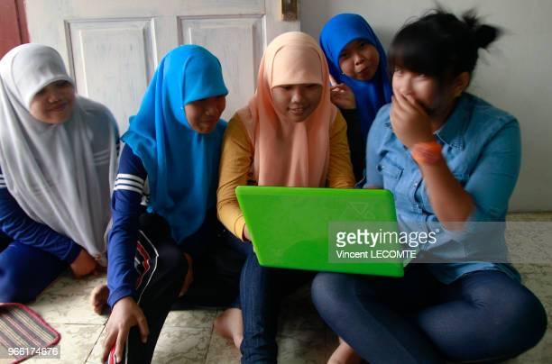 Groupe dadolescentes indonésiennes dont certaines sont voilées jouant sur un ordinateur portable à l'école de Basca à Painan au sud de lîle de...