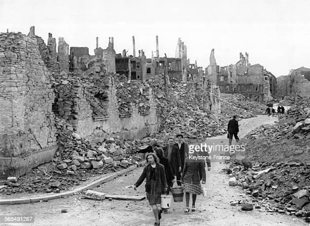 Groupe de femmes un seau à la main et d'hommes sur une route entre les décombres de la ville à Mannheim en Allemagne le 2 avril 1945