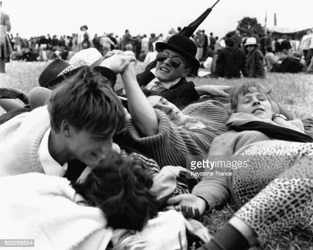 Groupe de jeunes beatniks allongés dans l'herbe pendant un rassemblement