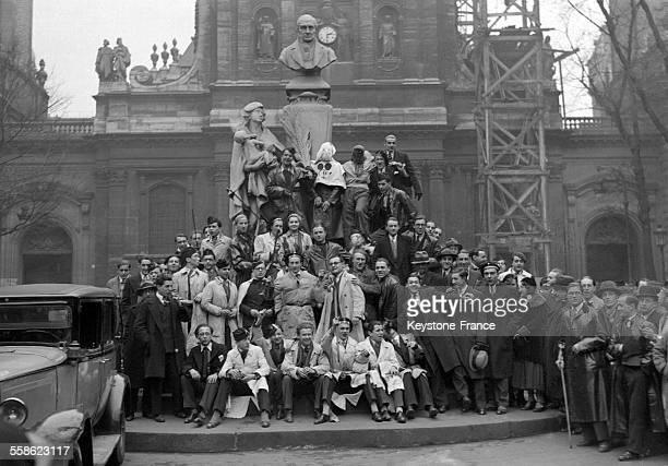 Groupe d'étudiants devant la statue d'Auguste Comte devant la Sorbonne au cours de leur monôme de la MiCarême à Paris France le 3 mars 1932