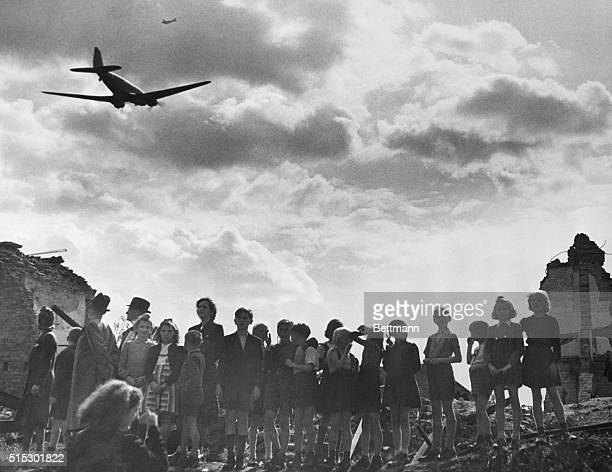 Grouped atop some of the ruins of warbattered Berlin German adults and children watch as an American plane flies overhead during an airlift bringing...