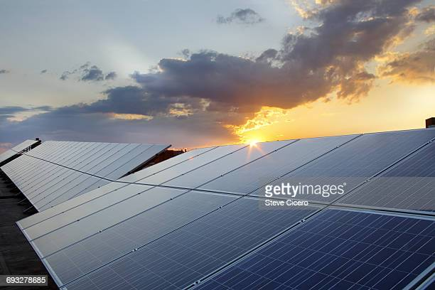 grouping of photovoltaic solar panels on rooftop - solar panel stock pictures, royalty-free photos & images