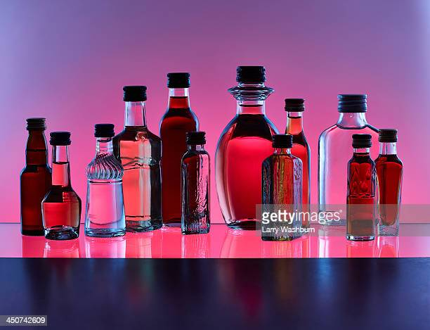 A grouping of various miniature bottles of alcohol without labels, back lit, colored background