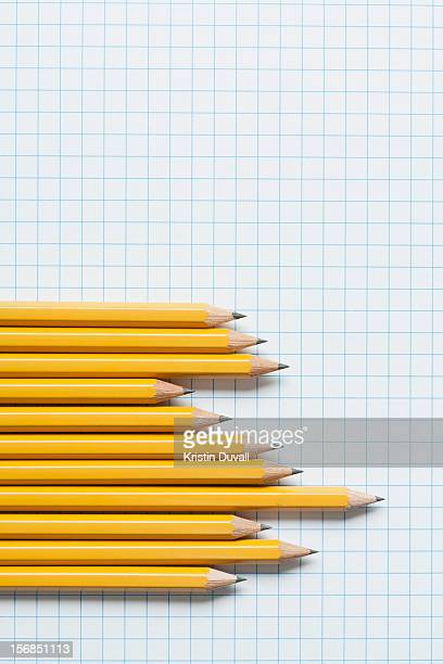 Grouping of yellow pencils in graph shape on graph paper