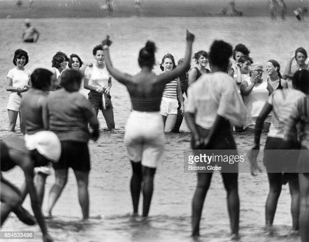 Groups of black women and white women separated by Boston police taunt one another in the water at Carson Beach in South Boston on Jul 24 1977 The...