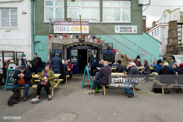 Groups of friends enjoy a drink together at The Front pub on Custom House Quay, on April 12, 2021 in Falmouth, England. England has taken a...