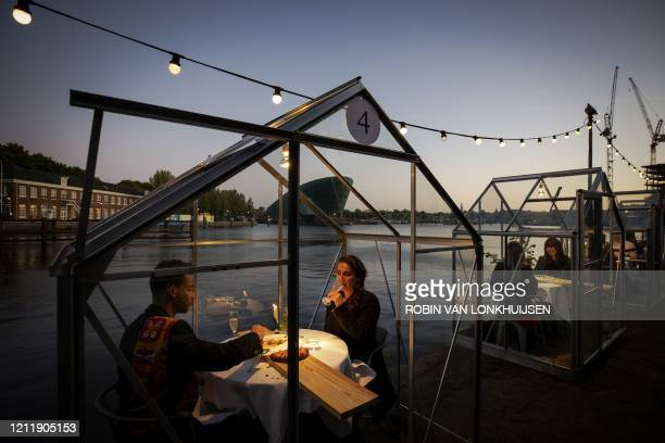 Groups of friends have dinner in a socalled quarantine greenhouses in Amsterdam on May 5 2020 as the country fights against the spread of the COVID19...