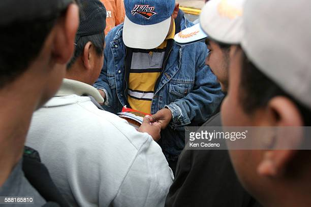 A groups of Latino day laborers look at another workers' photos as they congregate near a 7Eleven store in Herndon Virginia about 30 miles west of...