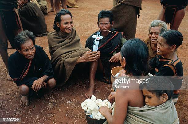 Groups of Montagnards sitting on the ground during Christmas celebration Some holding toys distributed by US Army soldiers