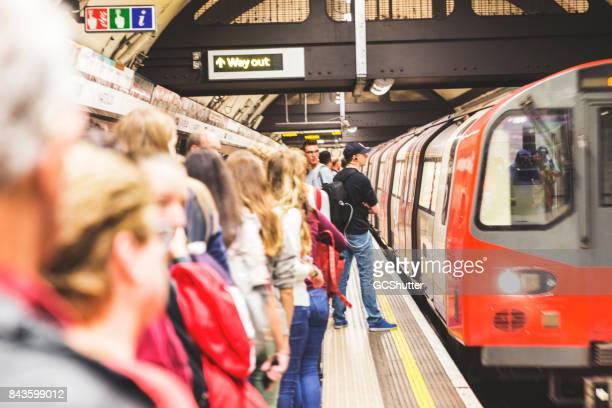"""""""mind the gap""""のルールを遵守することを遅く列車を待っている人々 のグループ - ロンドン地下鉄 ストックフォトと画像"""