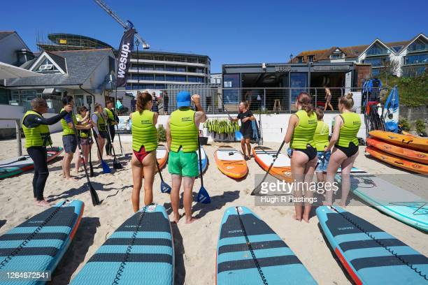 Groups of people prepare to take out paddle boards on Gyllyngvase Beach on August 8 2020 in Falmouth Cornwall England The RNLI has called on...
